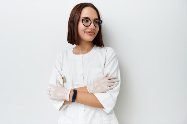 Pasante médico joven feliz mirando a otro lado mientras posa sobre fondo blanco con los brazos cruzados. retrato profesional. dia internacional del medico