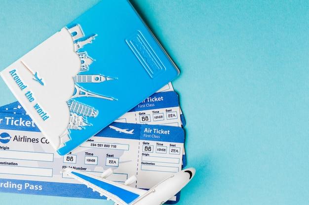 Pasaporte, avión y boleto aéreo en un azul.