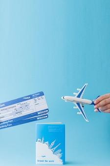 Pasaporte, avión y boleto aéreo en mano de mujer sobre un fondo azul. concepto de viaje, espacio de copia