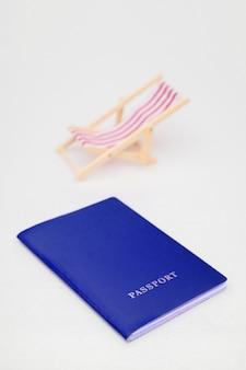 Pasaporte azul y silla de playa roja en un fondo blanco.