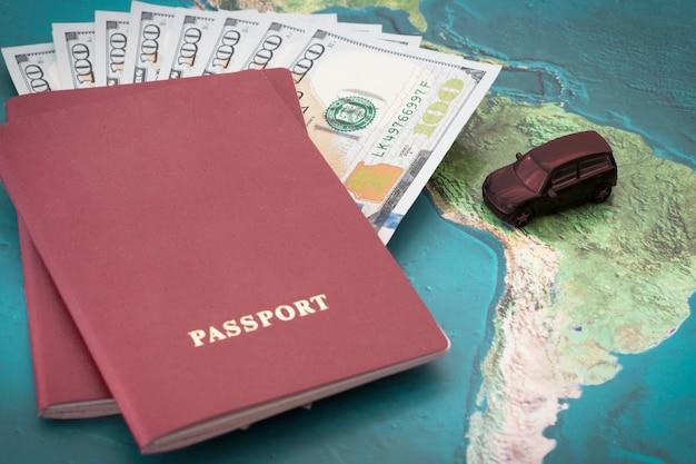 Pasaporte con billetes de cien dólares dentro y coche de juguete en el fondo del mapa mundial