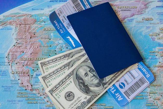 Pasaporte, boletos y dinero en el mapa.
