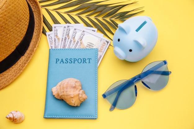 Pasaporte con dinero, gafas de sol y hucha en superficie amarilla. concepto de preparación de vacaciones de verano