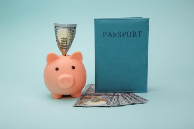 Pasaporte con dinero y hucha sobre fondo azul. ahorre para viajar