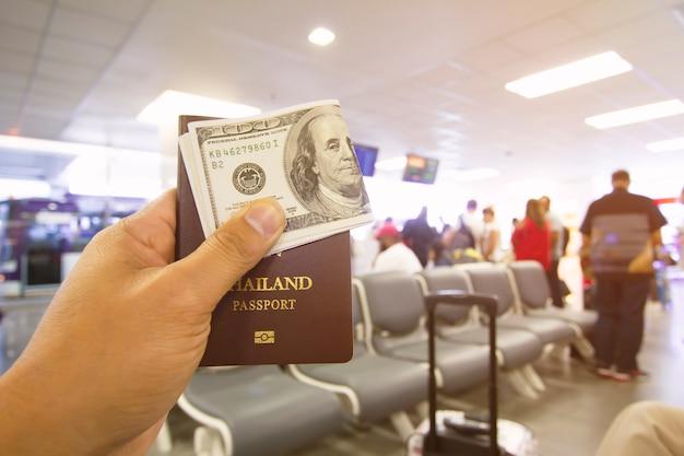 Pasaporte y dólar en manos masculinas sentado en el aeropuerto.