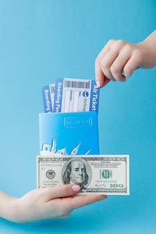 Pasaporte, dólares y boleto aéreo en mano de mujer. concepto de viaje