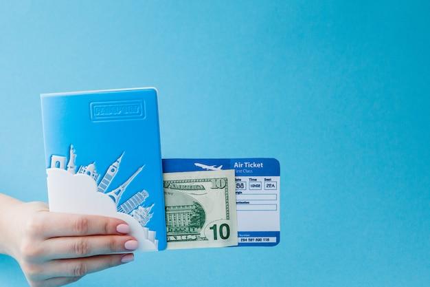 Pasaporte, dólares y boleto aéreo en mano de mujer sobre un fondo azul. concepto de viaje, espacio de copia