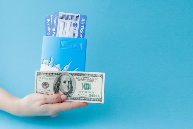 Pasaporte, dólares y boleto aéreo en mano de mujer