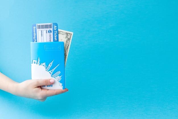 Pasaporte, dólares y boletos aéreos en mano de mujer.