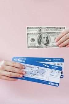 Pasaporte, dólares y boletos de avión en manos de mujeres.