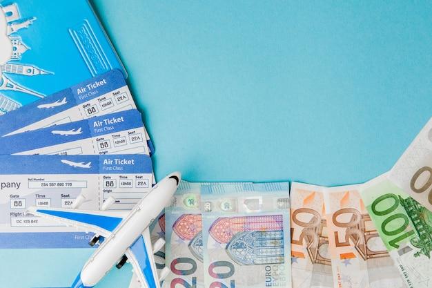 Pasaporte, dólares y euros, avión y boleto aéreo.