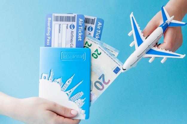 Pasaporte, euro, avión y boleto aéreo en mano de mujer sobre un fondo azul. concepto de viaje, espacio de copia