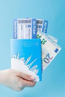 Pasaporte, euro y billete de avión en mano de mujer