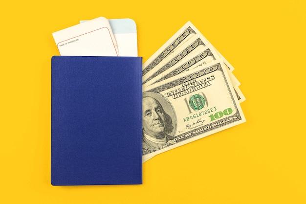 Pasaporte internacional con tarjeta de embarque de la aerolínea y dinero para viajar, escritorio de oficina amarillo y vista superior de la mesa