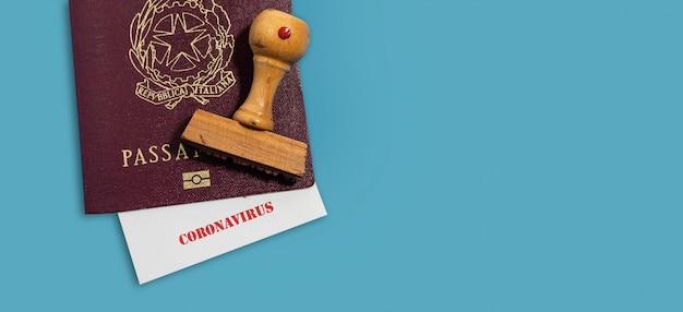 Pasaporte italiano con sello y papel con letras de coronavirus