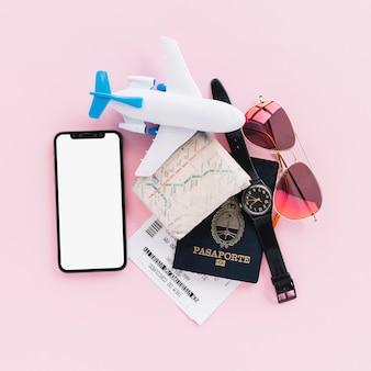 Pasaporte; mapa; entradas; avión de juguete; reloj de pulsera; teléfono móvil y gafas de sol sobre fondo rosa