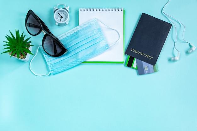 Pasaporte y máscara médica sobre un fondo azul concepto de viaje seguro durante la pandemia de coronavirus