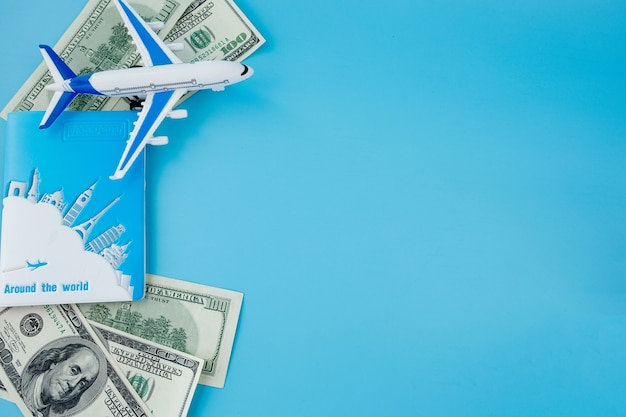 Pasaporte con modelo de avión de pasajeros y dólares sobre fondo azul. concepto de viaje