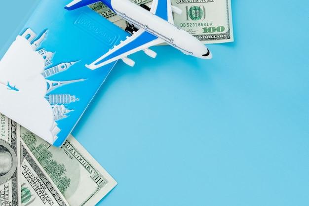 Pasaporte con modelo de avión de pasajeros y dólares en superficie azul
