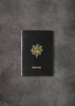 Pasaporte negro genérico aislado sobre fondo de hormigón oscuro
