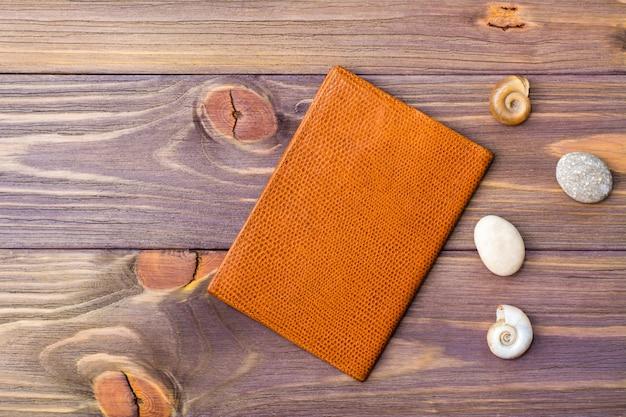 Pasaporte, piedra y conchas marinas sobre un fondo de madera