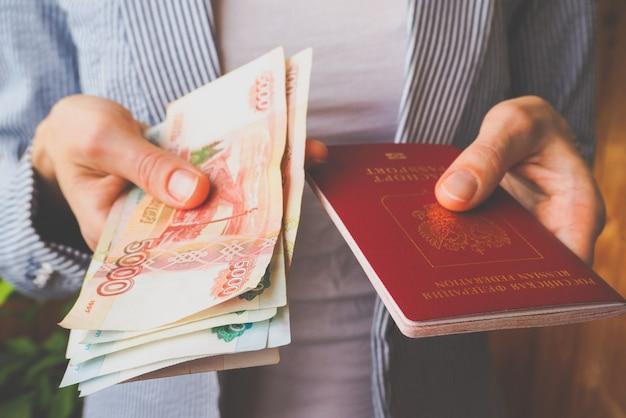 Pasaporte ruso y nota rublos en las manos.