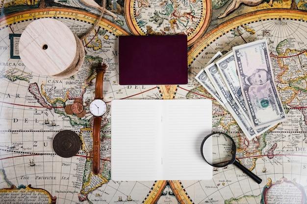 Pasaporte y diario con equipos antiguos en el mapa mundial