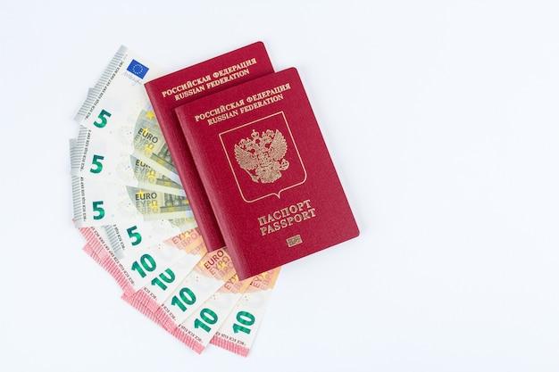Pasaportes y billetes en euros en la vista superior blanca