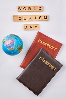 Pasaportes internacionales y globo. día mundial del turismo a partir de bloques de letras de madera sobre fondo blanco.