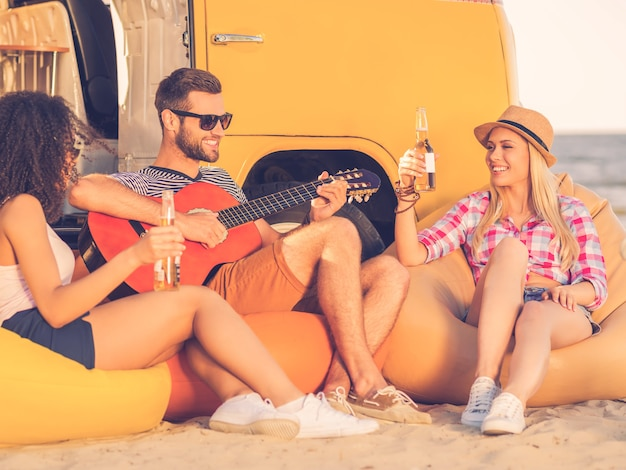 Pasar un buen rato con amigos. feliz joven tocando la guitarra mientras dos mujeres jóvenes sentadas cerca de él y bebiendo cerveza con una minivan amarilla en el fondo