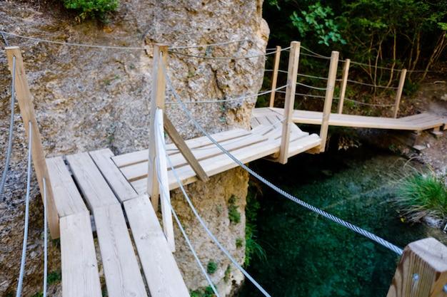 Pasarela de madera junto a unas rocas en el cauce de un río para facilitar el paso de turistas y senderistas.