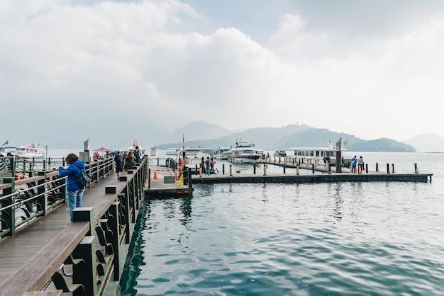 Pasarela de madera que conduce al barco en el lago sun moon con montañas y nubes