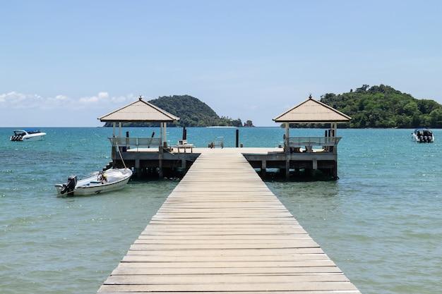 Pasarela de madera que conduce al mar desde la playa con lanchas rápidas y una isla de fondo.