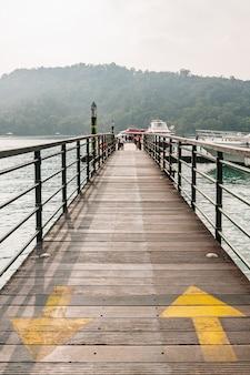 Pasarela de madera que lleva al barco con flechas amarillas en el lago sun moon