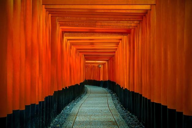 La pasarela de puertas torii rojas en el santuario fushimi inari taisha en kyoto, japón.