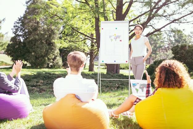 Pasarlo bien. contenido chica elegante de pie en el tablero y discutiendo su proyecto con sus compañeros de grupo