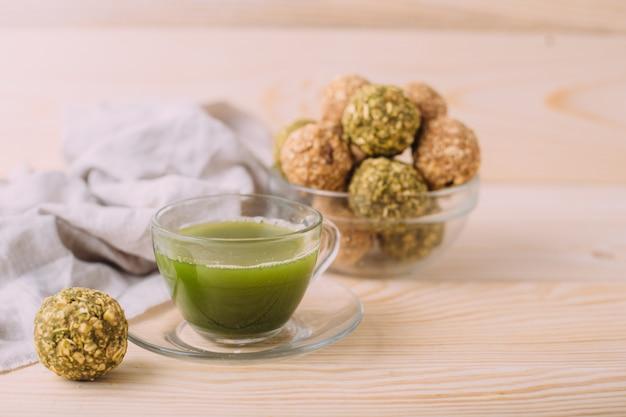 Pasas de almendra bolas de felicidad miel. bocadillos saludables de avena bolas energéticas con avena mantequilla de almendras y miel. taza de té matcha