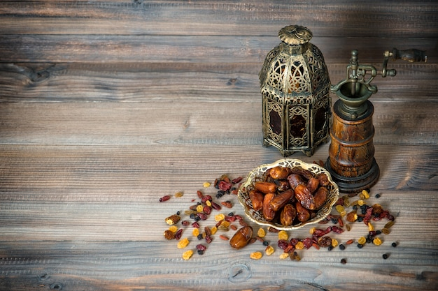 Pasas y dátiles sobre fondo de madera. árabe hasta la vida con molino y latern oriental vintage. concepto de comida. imagen en tonos retro