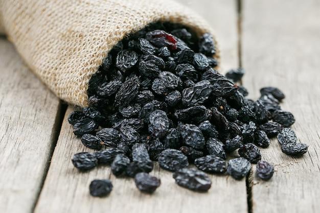 Pasas negras en bolsa de arpillera sobre mesa de madera gris
