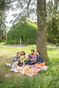 Pasatiempo. grupo de jóvenes sentados en cuadros con comida, bebidas y guitarra descansando en un picnic en el parque verde
