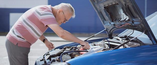 Un pasatiempo del hombre mayor, anciano arreglando el motor del automóvil al aire libre