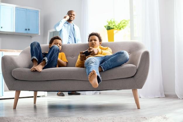 Pasatiempo pacífico. encantadores niños pequeños sentados en el sofá y jugando videojuegos mientras su padre tiene una conversación telefónica en el fondo