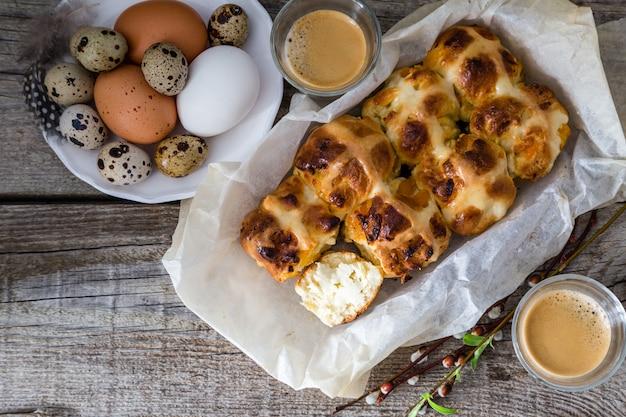Pascua bollos cruzados calientes con huevos fondo de madera rústica