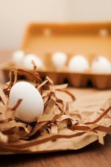 Pascua, huevos blancos sobre papel marrón y sobre bandeja de huevos sobre mesa de madera