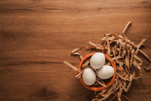 Pascua, huevos blancos sobre papel marrón sobre mesa de madera