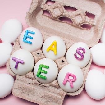 Pascua de las letras en los huevos blancos en estante