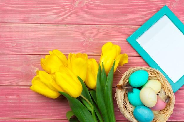 Pascua marco de madera con huevos de pascua y tulipanes en colores