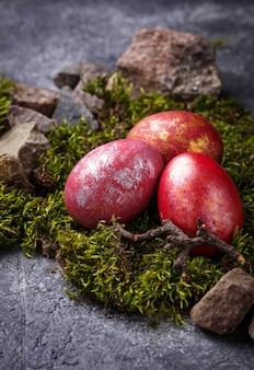 Pascua pintó huevos rojos en musgo