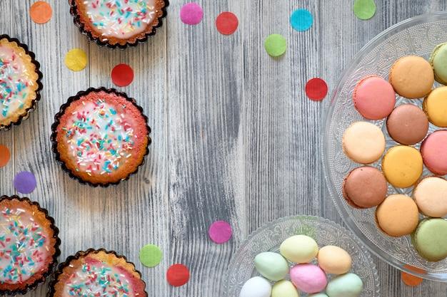 Pascua plana con macarons, muffins y huevos de mazapán en una bandeja decorativa sobre madera gris texturizada