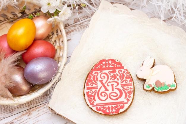 Pascua de resurrección. huevos de colores en una canasta. conejo de pan de jengibre de pascua, huevo en una canasta. sobre un fondo de madera clara.